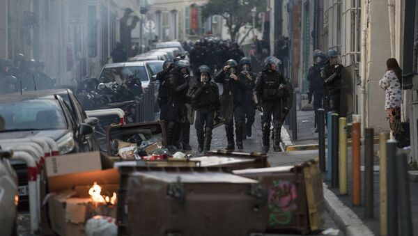 Police approach a barricade made by protesters during a yellow vest demonstration marking the one year anniversary of the movement in Marseille, southern France, Saturday, Nov. 16, 2019.  Police are deployed around key sites in Paris as France's yellow vest protesters prepare to mark the first anniversary of their sometimes-violent movement for economic justice. - Sputnik International