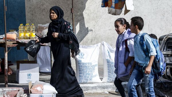 Palestinian pupils walk by a women receiving food aid from a United Nations Relief and Works Agency (UNRWA) distribution centre in the southern Gaza Strip refugee camp of Rafah, on November 17, 2019.  - Sputnik International