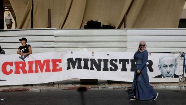 A woman walks past a banner depicting Israeli Prime Minister Benjamin Netanyahu and the words Crime Minister outside the Justice Ministry - Sputnik International