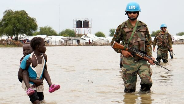 A girl holding a child walks past UN peacekeepers, after heavy rains and floods forced hundreds of thousands of people to leave their homes, in the town of Pibor, Boma state, South Sudan, November 6, 2019. - Sputnik International