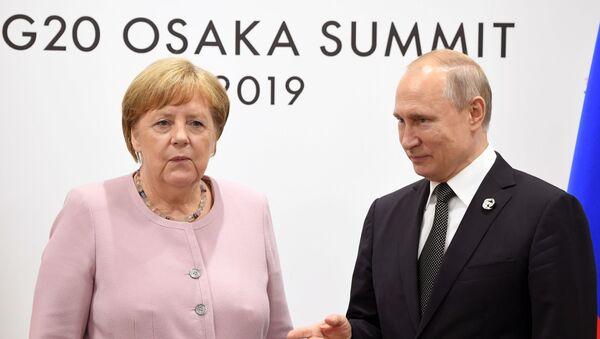 Russian President Vladimir Putin and German Chancellor Angela Merkel during a G20 meeting at the INTEX Osaka International Exhibition Center. - Sputnik International