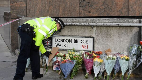 A police officer places a floral tribute near the scene of a stabbing on London Bridge, in London - Sputnik International