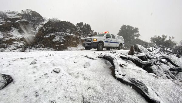 This photo tweeted by the Santa Barbara County Fire Department shows a Santa Barbara Fire Department truck along E. Camino Cielo as snow falls at the 3,500 foot level on the fire footprint in Santa Barbara, Calif. Thursday, Nov. 28, 2019. Wintry weather temporarily loosened its grip across much of the U.S. just in time for Thanksgiving, after tangling holiday travelers in wind, ice and snow and before more major storms descend Friday. (Mike Eliason/Santa Barbara County Fire via AP) - Sputnik International