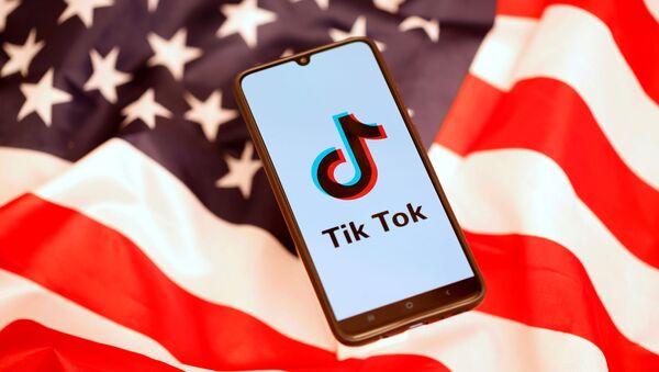 TikTok logo is displayed on the smartphone while standing on the U.S. flag - Sputnik International