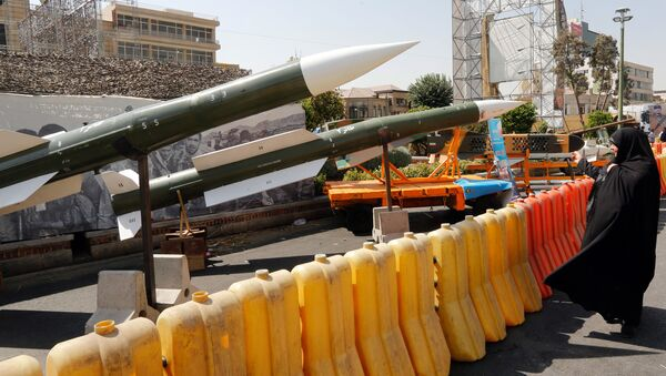 An Iranian woman looks at Taer-2 missile during a street exhibition by Iran's army and paramilitary Revolutionary Guard celebrating  Defence Week marking the 39th anniversary of the start of 1980-88 Iran-Iraq war, at the Baharestan Square in Tehran, on September 26, 2019 - Sputnik International