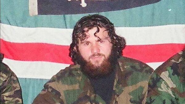 Zelimkhan Khangoshvili is pictured against the backdrop of the flag of the unrecognised Chechen Republic of Ichkeria during the Chechen conflict. - Sputnik International