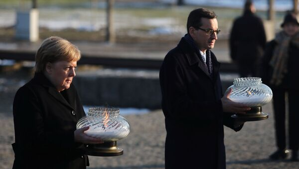 Polish Prime Minister Mateusz Morawiecki and German Chancellor Angela Merkel hold candles at the Monument to the Victims at the former Nazi German concentration and extermination camp Auschwitz II-Birkenau near Oswiecim, Poland December 6, 2019. - Sputnik International