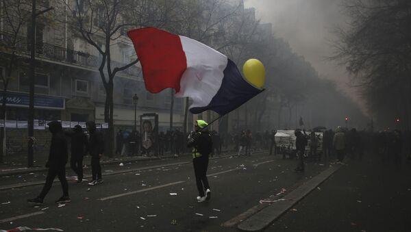 A man waves a French flag during a demonstration in Paris, Thursday, Dec. 5, 2019. Small groups of protesters are smashing store windows, setting fires and hurling flares in eastern Paris amid mass strikes over the government's retirement reform. - Sputnik International