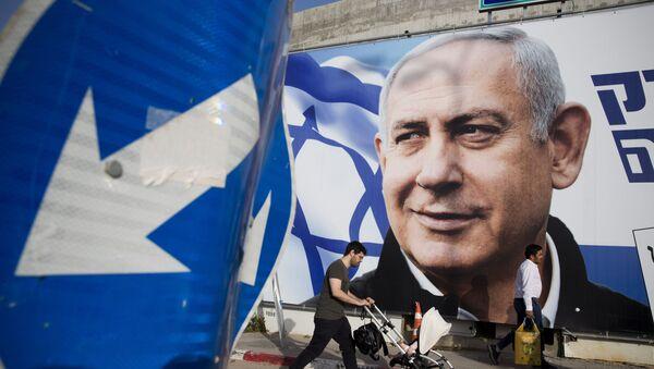 FILE - In this April 7, 2019 file photo, a man walks by an election campaign billboard showing Israel's Prime Minister Benjamin Netanyahu, the Likud party leader, in Tel Aviv, Israel.  - Sputnik International