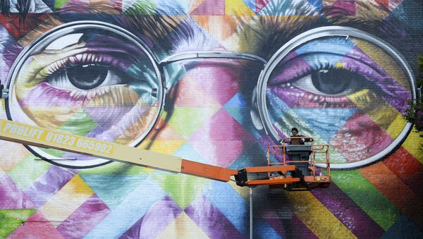 A graffiti artist works on a huge mural of former Beatle John Lennon - Sputnik International
