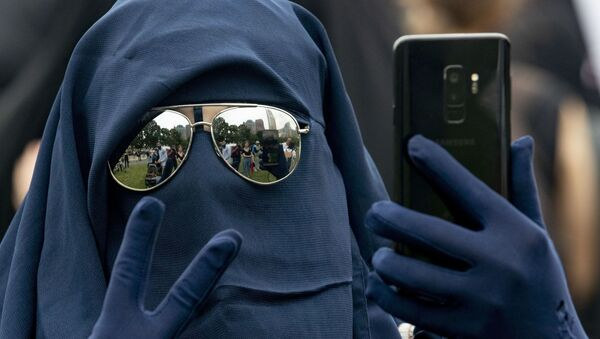 A woman wearing a niqab takes a selfie while flashing the victory sign as she takes part in a demonstration against a ban on face-covering veils in The Hague on 9 August 2019. - Sputnik International