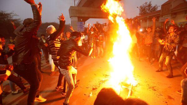 Demonstrators burn an effigy depicting Prime Minister Narendra Modi during a protest against a new citizenship law, outside Jamia Millia Islamia university in New Delhi, India, December 16, 2019.  - Sputnik International