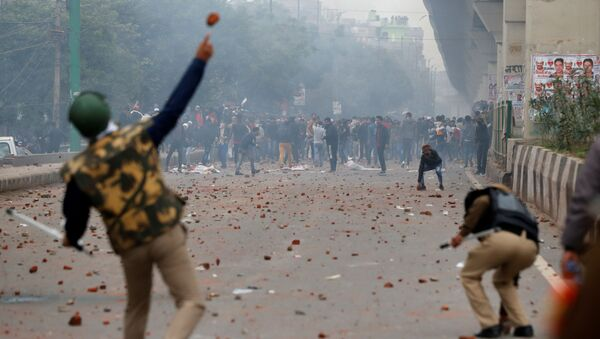 A riot police officer throws a piece of brick towards demonstrators during a protest against a new citizenship law in Seelampur, area of Delhi, India  December 17, 2019 - Sputnik International