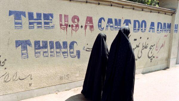 Two Iranian women wearing chadors walk past an anti-American slogan in a street of the Djarmaran district where lived Ayatollah Khomeini on July 30, 1989 - Sputnik International