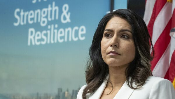 Democratic presidential candidate U.S. Rep. Tulsi Gabbard, D-Hawaii, listens as family members of victims of the terrorist attacks on 9/11 speak during a news conference at the 9/11 Tribute Museum, Tuesday, Oct. 29, 2019, in New York. - Sputnik International