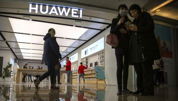 In this Nov. 20, 2019, photo, people stand outside of a Huawei store at a shopping mall in Beijing - Sputnik International