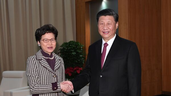 Chinese President Xi Jinping shakes hands with Hong Kong Chief Executive Carrie Lam, during their meeting on the eve of the 20th anniversary of the former Portuguese colony's return to China, in Macau, China December 19, 2019.  - Sputnik International