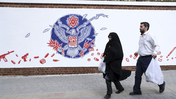 People walk past a satirical drawing of the Great Seal of the United States after new anti-U.S. murals on the walls of former U.S. embassy unveiled in a ceremony in Tehran, Iran, Saturday, Nov. 2, 2019 - Sputnik International