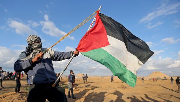 A Palestinian demonstrator uses a sling during an anti-Israel protest at the Israel-Gaza border fence, in the southern Gaza Strip December 6, 2019. - Sputnik International