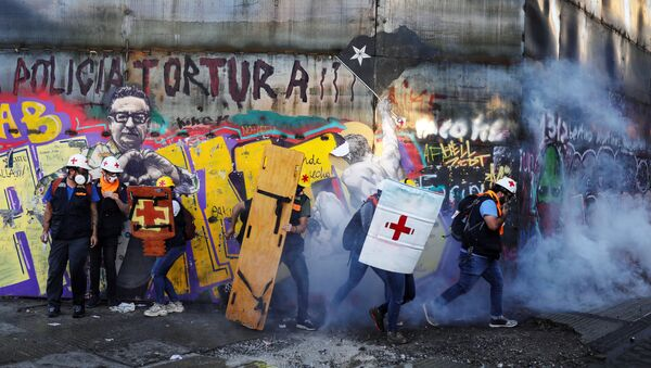 Medical volunteers move amid tear gas during a protest against Chile's government in Santiago, Chile December 20, 2019 - Sputnik International