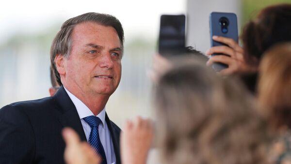 Brazil's President Jair Bolsonaro poses for pictures as he leaves the Alvorada Palace in Brasilia, Brazil December 12, 2019 - Sputnik International