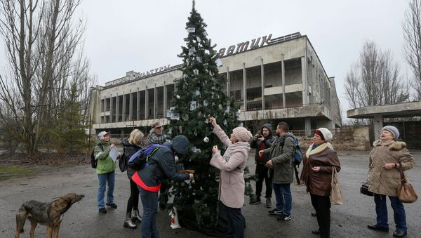 Former residents of Pripyat located near the Chernobyl Nuclear Power Plant decorate a Christmas tree, which was installed in the main square of the ghost town for the first time since 1985, in Pripyat, Ukraine December 25, 2019 - Sputnik International