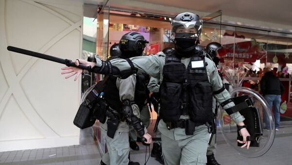 A riot police officer gestures as anti-government demonstrator take part in a protest in Sheung Shui shopping mall in Hong Kong, China, December 28, 2019 - Sputnik International