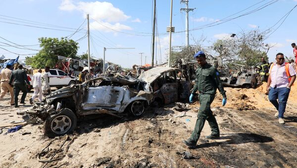 A Somali police officer walks past a wreckage at the scene of a car bomb explosion at a checkpoint in Mogadishu - Sputnik International