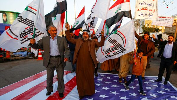 Iraqi people walk on a U.S. flag in a protest after an airstrike at the headquarters of Kataib Hezbollah militia group in Qaim, in the holy city of Najaf, Iraq December 30, 2019. - Sputnik International