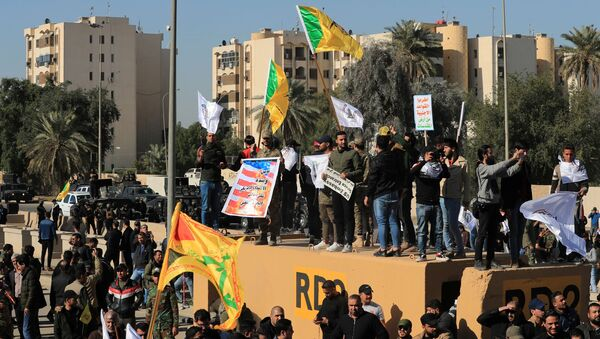 Protesters and militia fighters gather to condemn air strikes on bases belonging to Hashd al-Shaabi (paramilitary forces), outside the main gate of the U.S. Embassy in Baghdad, Iraq December 31, 2019 - Sputnik International