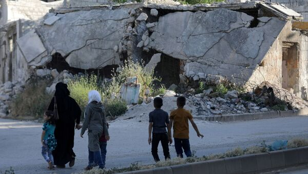 People walk near rubble of damaged buildings in the city of Idlib, Syria May 27, 2019. Picture taken May 27, 2019. - Sputnik International
