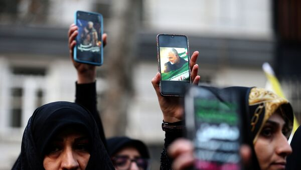 Iranian demonstrators hold up mobile phones showing the picture of the late Iranian Major-General Qassem Soleimani, during a protest against the assassination of Soleimani, head of the elite Quds Force, and Iraqi militia commander Abu Mahdi al-Muhandis, who were killed in an air strike at Baghdad airport, in front of United Nation office in Tehran, Iran January 3, 2020.  - Sputnik International