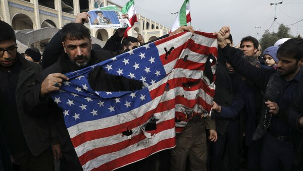 Protesters burn a U.S. flag during a demonstration over the U.S. airstrike in Iraq - Sputnik International