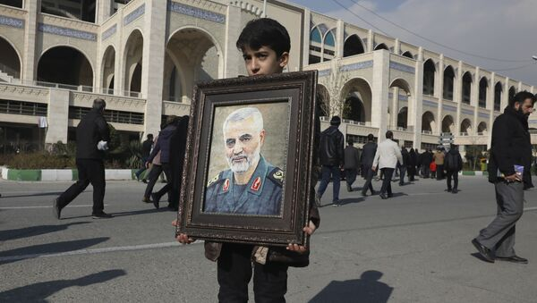 A boy carries a portrait of Iranian Revolutionary Guard Gen. Qassem Soleimani - Sputnik International