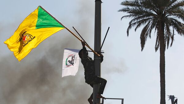 A member of Hashd al-Shaabi (paramilitary forces) holds a flag of Kataib Hezbollah militia group during a protest to condemn air strikes on their bases, in Baghdad, Iraq December 31, 2019.  - Sputnik International