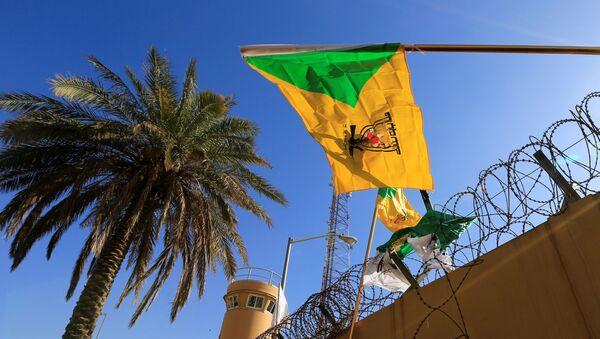 member of Hashd al-Shaabi (paramilitary forces) holds a flag of Kataib Hezbollah - Sputnik International