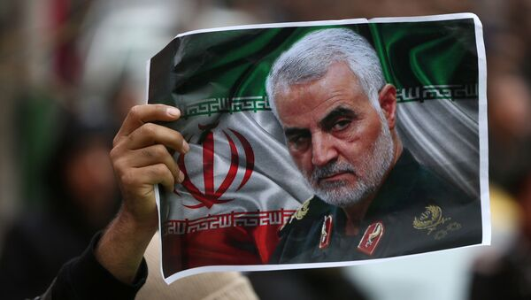 An Iranian holds a picture of late General Qassem Soleimani, head of the elite Quds Force, who was killed in an air strike at Baghdad airport, as people gather to mourn him in Tehran, Iran January 4, 2020.  - Sputnik International