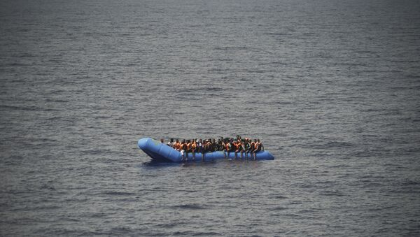 Migrants aboard a blue plastic boat in the Mediterranean Sea - Sputnik International