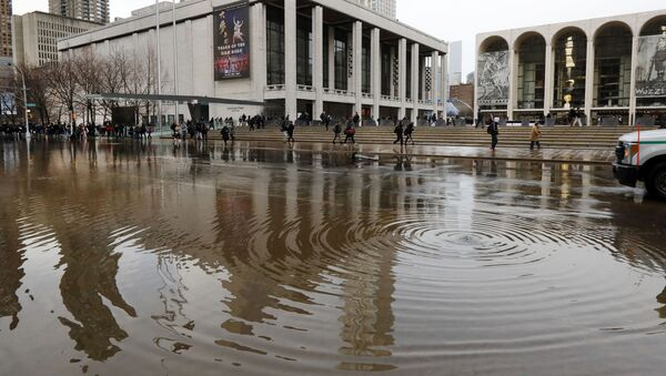 New York's Lincoln Center for the Performing Arts is reflected in a flooded street, in New York, Monday, Jan. 13, 2020. A water main break flooded streets on Manhattan's Upper West Side near Lincoln Center and hampered subway service during the Monday morning rush hour. (AP Photo/Richard Drew) - Sputnik International