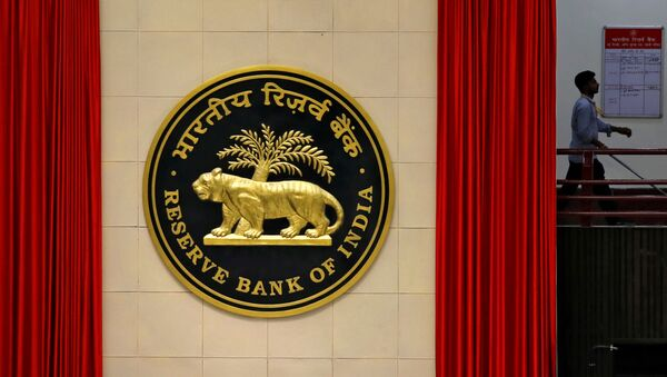 A worker walks past the logo of Reserve Bank of India (RBI) inside its office in New Delhi, India July 8, 2019 - Sputnik International