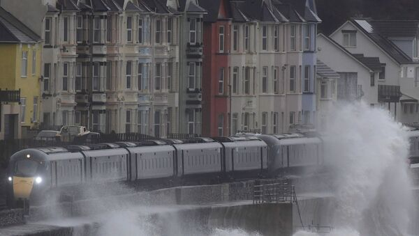 Large waves hit the sea wall with Storm Brendan bringing high winds and heavy rain, as a train passes through Dawlish, southwest Britain, January 14, 2020.  - Sputnik International