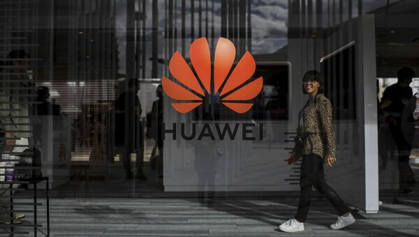 A woman walks past the logo of Chinese telecom giant Huawei during the Web Summit in Lisbon on November 6, 2019 - Sputnik International