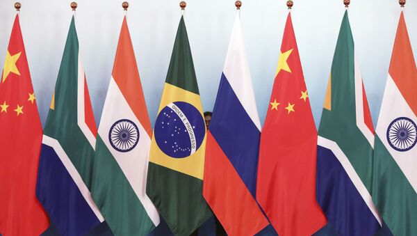 Staff worker stands behinds national flags of Brazil, Russia, China, South Africa and India to tidy the flags ahead of a group photo during the BRICS Summit at the Xiamen International Conference and Exhibition Center in Xiamen, southeastern China's Fujian Province, Monday, Sept. 4, 2017. - Sputnik International
