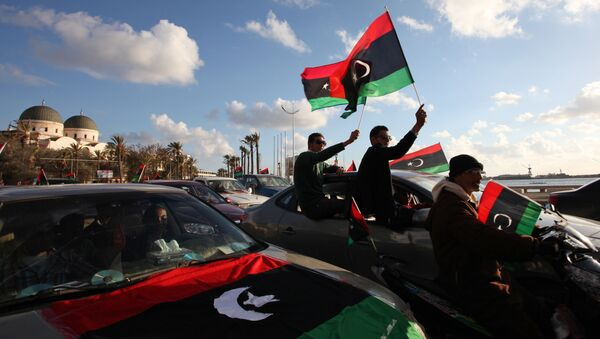 Libyans wave the national flag during commemorations to mark the second anniversary of the revolution that ousted Moammar Gadhafi in Benghazi, Libya, Friday, Feb, 15, 2013 - Sputnik International