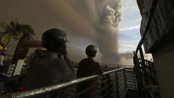 In this Jan. 12, 2020, photo, people watch plumes of smoke and ash rise from as Taal volcano erupts in Tagaytay, Cavite province, outside Manila, Philippines - Sputnik International