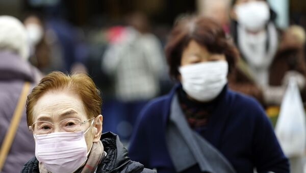 Pedestrians wear protective masks as they walk through a shopping district in Tokyo Thursday, Jan. 16, 2020. Japan's government said Thursday a man treated for pneumonia after returning from China has tested positive for the new coronavirus identified as a possible cause of an outbreak in the Chinese city of Wuhan.  - Sputnik International