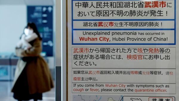 A woman wearing a mask walks past a quarantine notice about the outbreak of coronavirus in Wuhan, China at an arrival hall of Haneda airport in Tokyo, Japan, January 20, 2020 - Sputnik International
