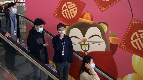 People wear face masks as they ride an escalator at the Hong Kong International Airport in Hong Kong, Tuesday, Jan. 21, 2020 - Sputnik International