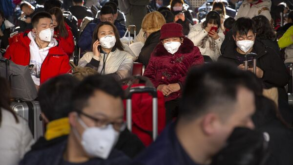 Travelers wear face masks as they sit in a waiting room at the Beijing West Railway Station in Beijing, Tuesday, Jan. 21, 2020 - Sputnik International