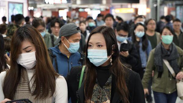 Passengers wear masks to prevent an outbreak of a new coronavirus in a subway station, in Hong Kong, Wednesday, Jan. 22, 2020 - Sputnik International